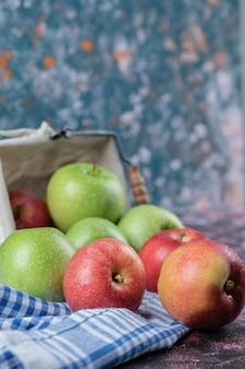 Czerwone i zielone jabłka na białym tle na niebieski ręcznik w kratkę.