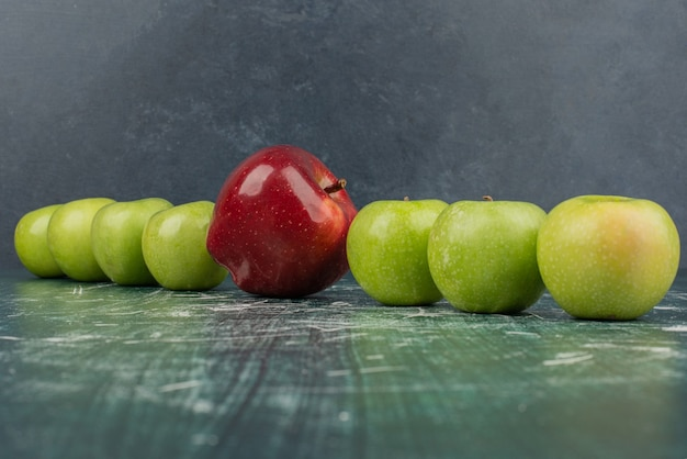 Czerwone i zielone jabłka na marmurowym stole.