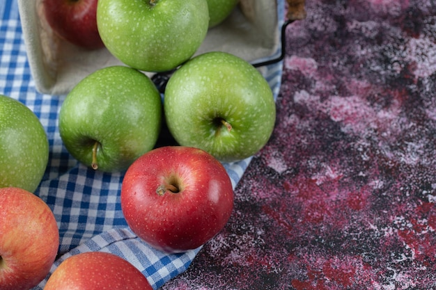 Czerwone i zielone jabłka na niebieskim ręczniku w kratkę.