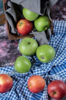 Czerwone i zielone jabłka na ręczniku w kratkę.