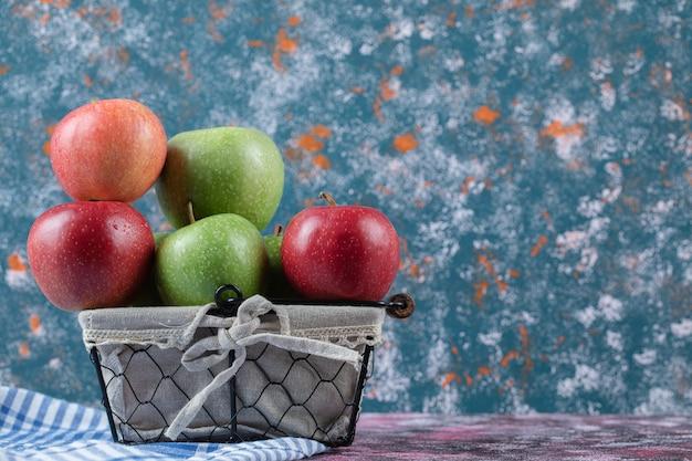 Czerwone i zielone jabłka w metalowym koszu