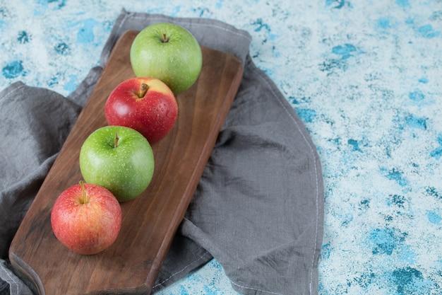 Czerwone i zielone jabłka z rzędu na drewnianej desce.