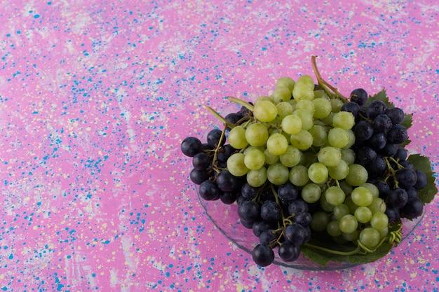 Czerwone i zielone kiście winogron w półmisku