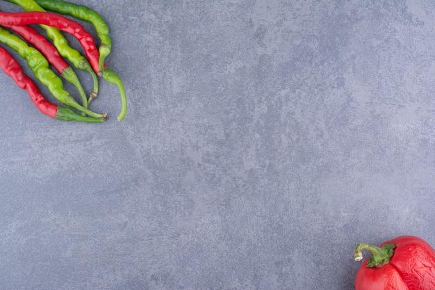 Czerwone i zielone ostre papryczki chili na ziemi