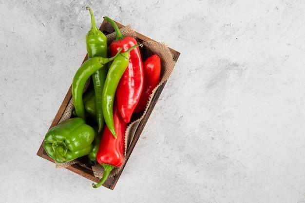 Czerwone i zielone papryczki chili w drewnianej tacy.