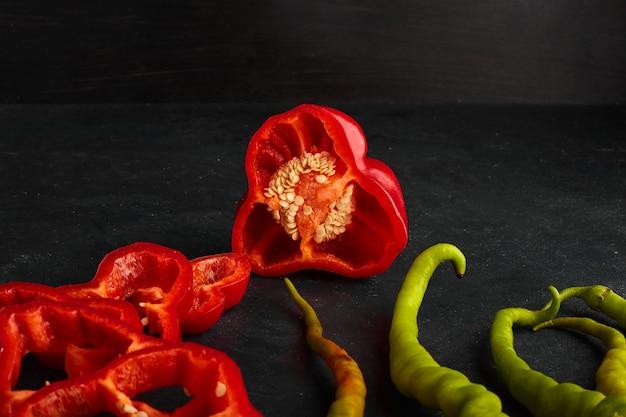 Czerwone i zielone papryczki chili w plasterkach i podawane na czarnej desce.