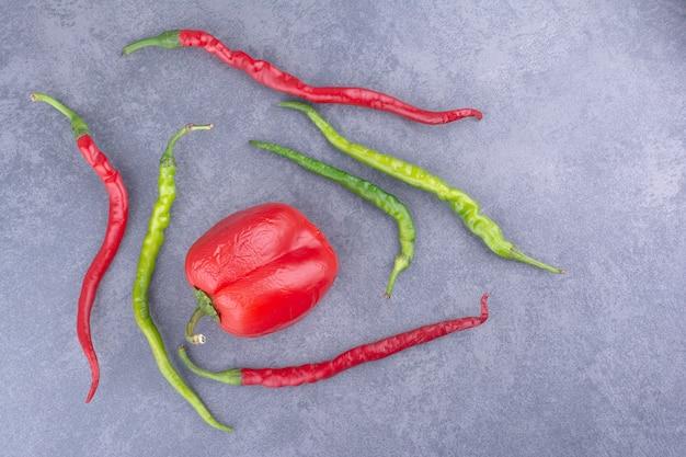 Czerwone i zielone papryki chili na szarym tle.