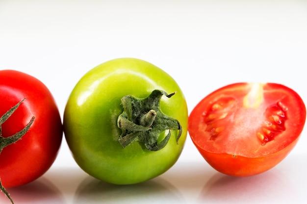 Czerwone i zielone pomidory na podłodze.
