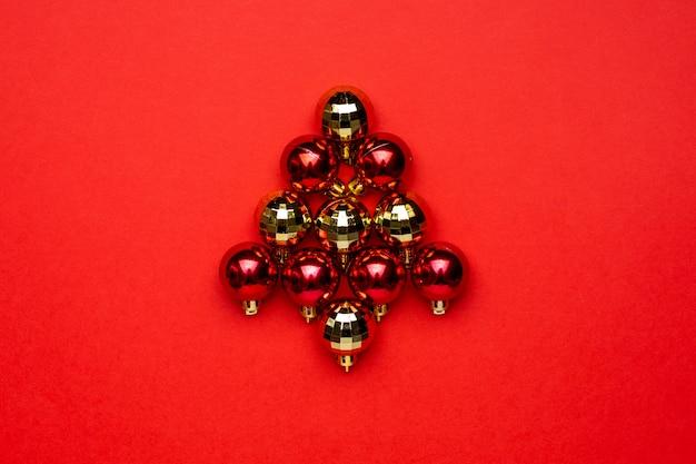 Czerwone i złote bombki na czerwonym tle. minimalna kompozycja w sezonie zimowym