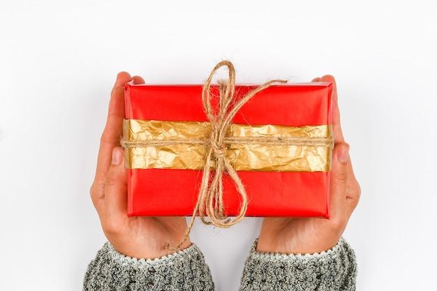Czerwone i złote opakowanie prezentowe w rękach. dzianina z kokardką na białej powierzchni. opakowanie na prezent diy. ręce kobiety dają zapakowany prezent. prezent świąteczny. widok z góry.