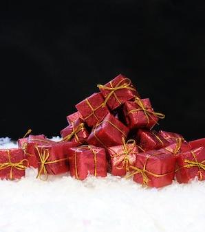 Czerwone i złote prezenty świąteczne w śniegu na czarnym tle