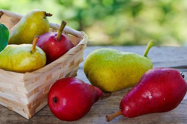 Czerwone i żółte gruszki w koszu na drewnianym stole z bliska