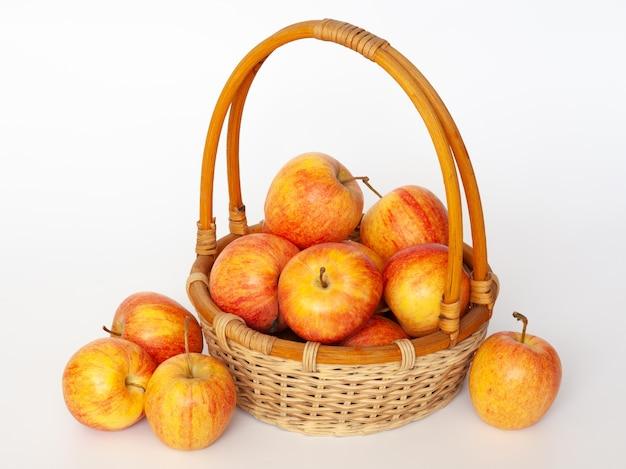 Czerwone i żółte jabłka w wiklinowym koszu. na białym tle