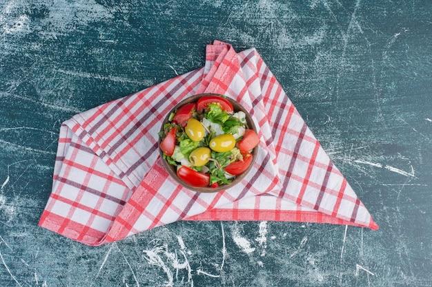 Czerwone i żółte pomidorki czereśniowe na białym tle na niebieskiej powierzchni.