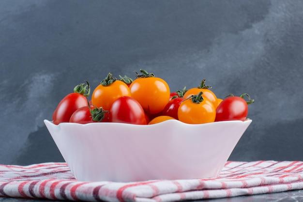 Czerwone i żółte pomidorki czereśniowe na niebieskiej powierzchni.