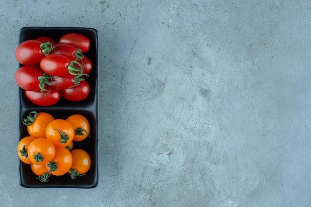 Czerwone i żółte pomidorki koktajlowe na czarnym półmisku.