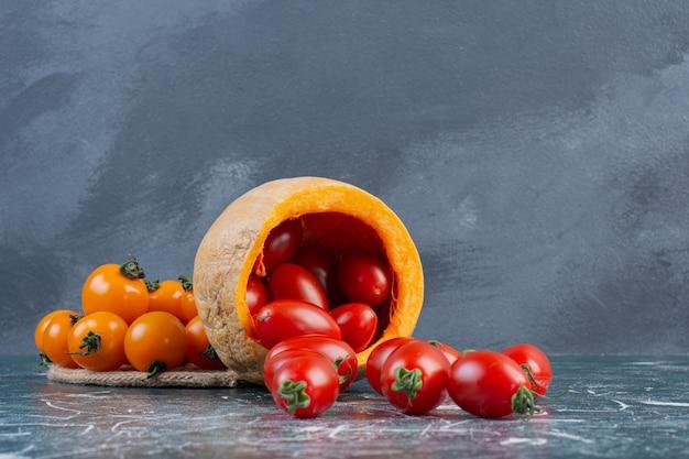 Czerwone i żółte pomidorki koktajlowe na niebieskim tle.