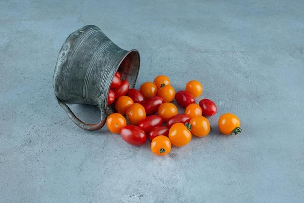 Czerwone i żółte pomidorki koktajlowe w metalowej doniczce.