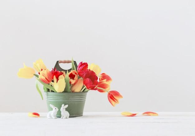 Czerwone i żółte tulipany w wiadrze i ceramiczny królik na białym tle