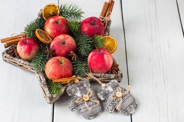 Czerwone jabłka, cynamon, gałęzie sosny i rękawiczki z dzianiny