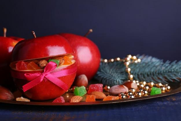 Czerwone jabłka faszerowane suszonymi owocami na metalowej tacy na kolorowym drewnianym stole