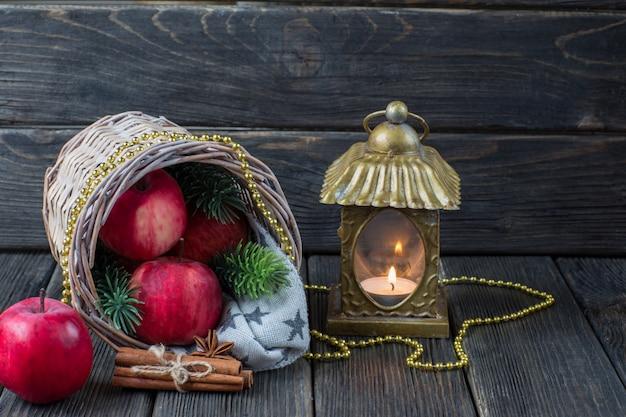 Czerwone jabłka, gałązki świerku, cynamonu, złote koraliki i stary świecznik
