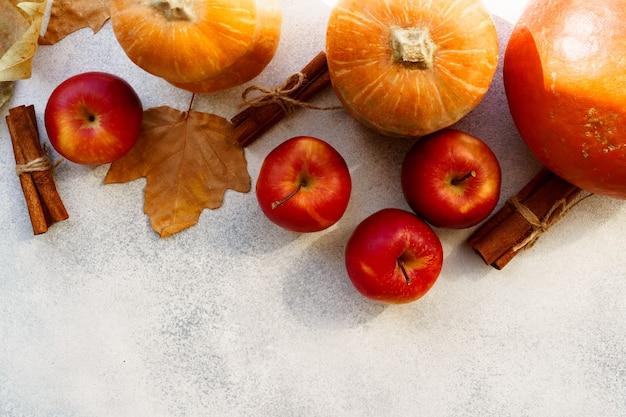 Czerwone jabłka i dynie z suchymi liśćmi i cynamonem na białym tle
