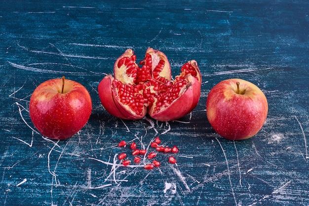 Czerwone jabłka i granat na niebieskiej przestrzeni.