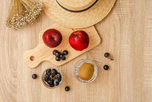 Czerwone jabłka i kiść czarnych winogron na desce, kiść czarnych winogron i owoców kiwi w szklance, słomkowym kapeluszu i trawach na drewnianej powierzchni stołu