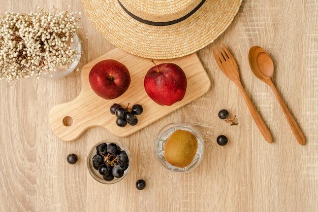 Czerwone jabłka i kiść czarnych winogron na desce, kiść czarnych winogron i owoców kiwi w szklance, słomkowym kapeluszu, trawiastych kwiatach oraz drewnianą łyżką i widelcem na drewnianej powierzchni stołu
