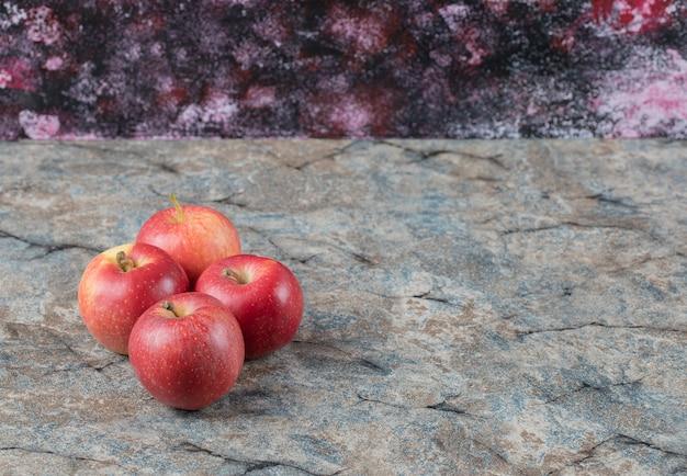 Czerwone jabłka na białym tle na betonowej powierzchni