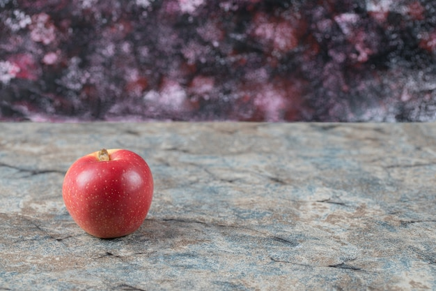 Czerwone jabłka na białym tle na powierzchni betonu