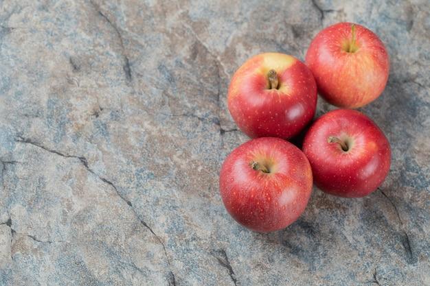 Czerwone jabłka na białym tle na szarym marmurze.