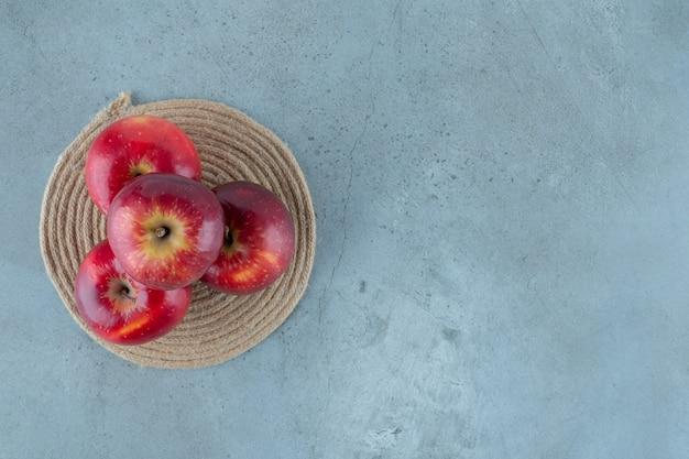 Czerwone jabłka na podstawce, na marmurowym stole.