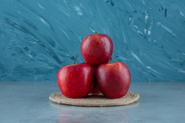 Czerwone jabłka na podstawce, na marmurowym tle.