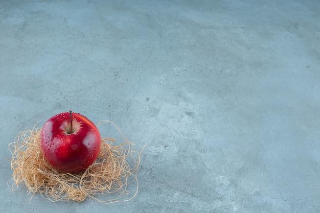 Czerwone jabłka na suchej słomie, na marmurowym tle. zdjęcie wysokiej jakości