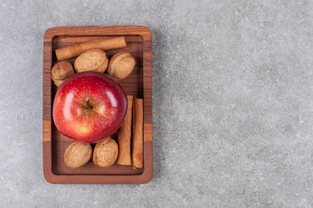 Czerwone jabłka, orzechy włoskie i laski cynamonu na drewnianym talerzu