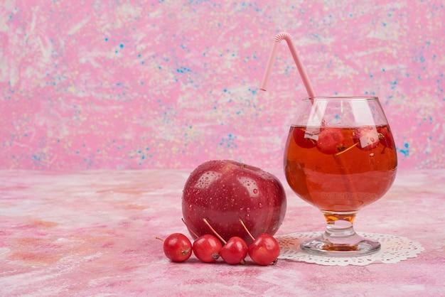 Czerwone jabłka popijając szklanką soku.