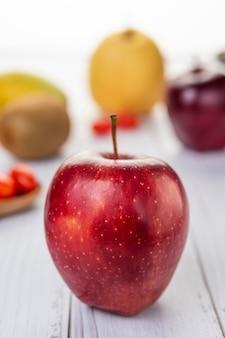 Czerwone jabłka umieszczone na drewnianej podłodze.
