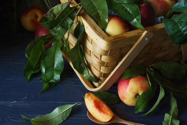 Czerwone jabłka w brązowym plecionym koszu