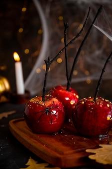 Czerwone jabłka w karmelu ze świątecznym wystrojem halloween to oryginalna uczta na świąteczny halloween