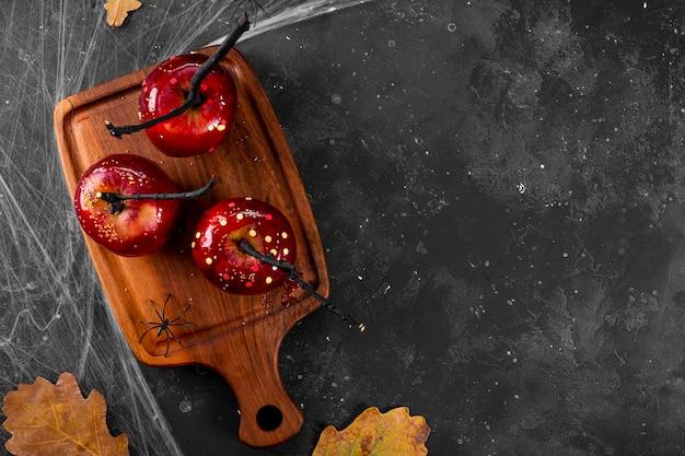 Czerwone jabłka w karmelu ze świątecznym wystrojem na halloween oryginalna uczta na świąteczny halloween