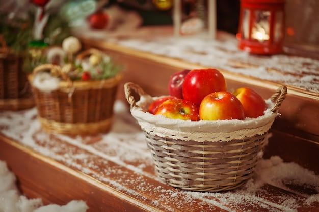Czerwone jabłka w koszu. tradycyjne ustawienie świąteczne. dekoracja świąteczna.