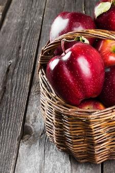 Czerwone jabłka w koszyku koralowym