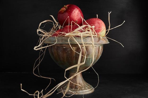 Czerwone jabłka w metalowej filiżance.