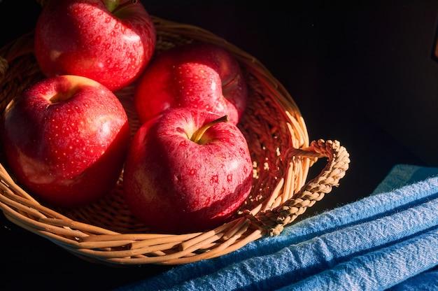 Czerwone jabłka w ręcznie robionym koszyku