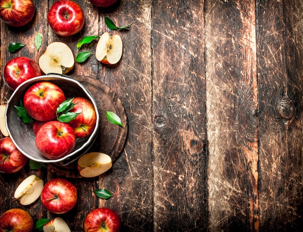 Czerwone jabłka w starym wiadrze. na drewnianym tle.
