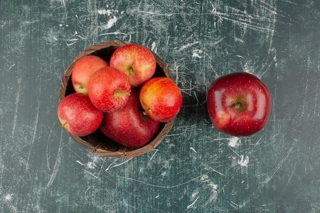 Czerwone jabłka w wiadrze na marmurowym stole.