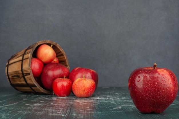 Czerwone jabłka wypadają z wiadra na marmurowym stole.