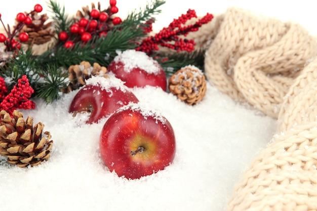 Czerwone jabłka z gałązkami jodły i szalik z dzianiny w śniegu z bliska